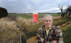 Councillor Harold Steeves in front of farmland owned by Adera Developments
